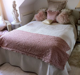 cream paisley patchwork bedspread with pink lace throw
