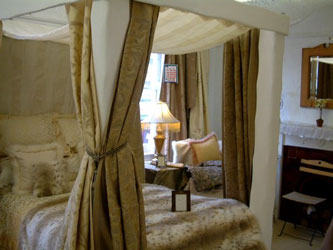 white four poster with taupe bed hangings and fur throw